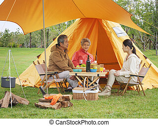 A happy family of three having a picnic outdoors