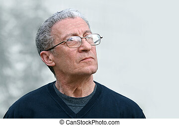A portrait of a senior man looking up