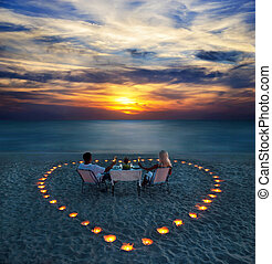 A young couple share a romantic dinner with candles heart on the sea sand beach