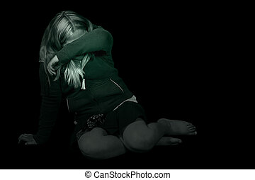 Black and white image of a young girl cowering in a dark room, hiding from the abuse