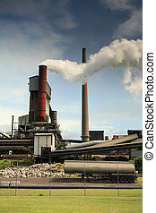 Steel mill smelter emitting toxic fumes and air pollutants billowing up and out of one of its many tall chimneys. Pollutants can vary and include hydrogen fluoride, sulfur dioxide, oxides of nitrogen, offensive and noxious smoke fumes, vapors, gases, and other toxins. A variety of heavy metals: lead...