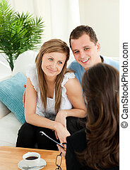 Affectionate couple listen to a saleswoman siting on a sofa in the living room