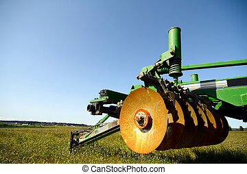 A heavy industrial agriculture machinery on an empty field