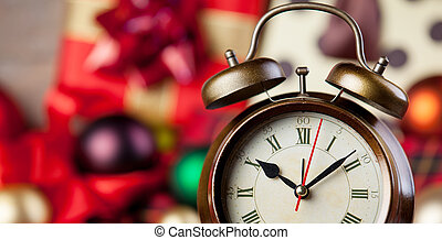 Alarm clock and christmas gifts on background.