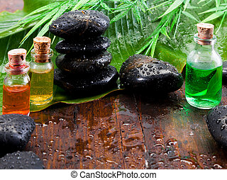 Bottles of essential oil plant extracts and smooth black massage stones in an aromatherapy spa treatment still life