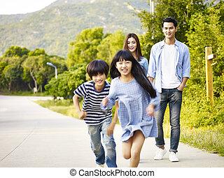 asian family relaxing in park