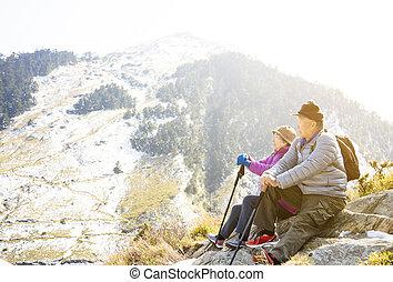 asian senior couple hiking on the mountain