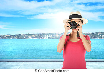 Asian woman in hat take a picture with her camera