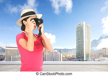 Asian woman in hat takes a picture of the modern city with her camera