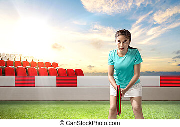 Asian woman with a tennis racket in her hands