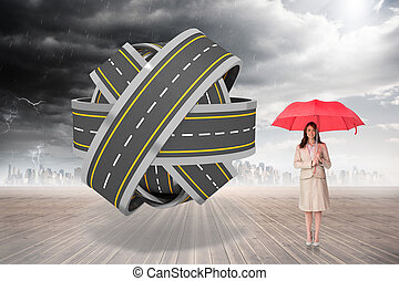 Attractive businesswoman holding red umbrella against tangled roads in a ball
