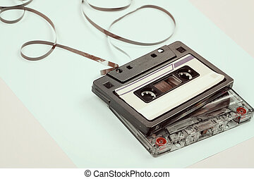 audio cassette with tangled tape on blue background, minimalistic composition.