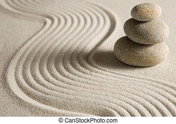 Stack of stones on raked sand; zen concept