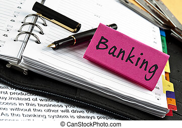 Banking note on agenda and pen