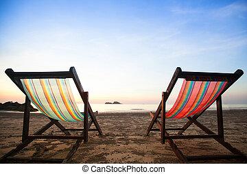 Beach chairs on sea coast.