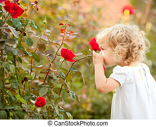 Beautiful child smelling rose against spring flowery background