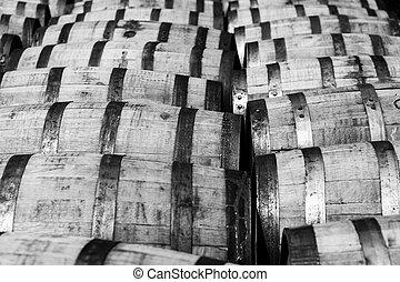Rows of oak bourbon barrels at a distillery warehouse