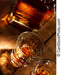 close up view of nice bottle and two glasses filled with whiskey