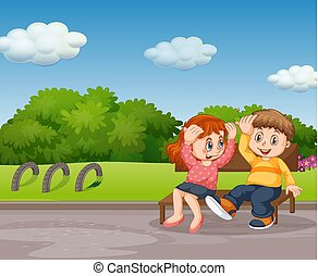 Boy and girl sitting in park