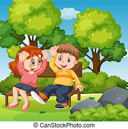Boy and girl sitting in park together