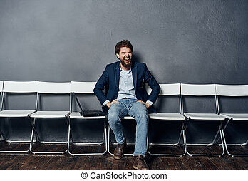 Business man in a suit sitting on a chair waiting laptop work office job interview