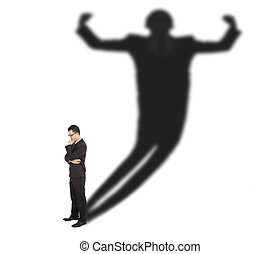 Business man standing and casting shadow of a strong man