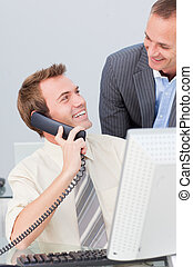 Businessman on phone talking to his colleague in the office