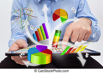 Businessman working on tablet computer - producing charts and reports
