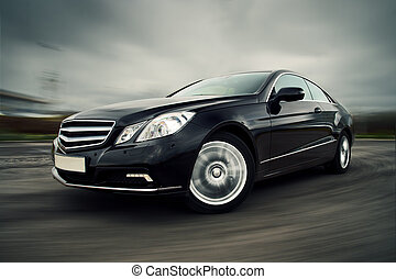 Front view of black luxury coupe driving fast