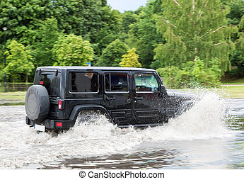 Car trying to drive against flood on the street in Gdansk, Poland.