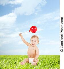 cute little boy playing with big lollipop
