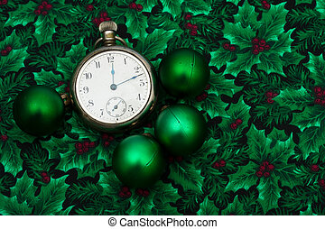 A pocket watch with green glass balls on a holly berry background, Christmas time
