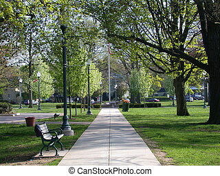 Springtime in a city park in Anytown, USA. Path lined with old-style lampposts leading to the flagpole, and a hat on the bench.