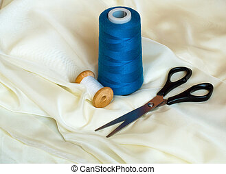 Close up shot of scissors and sewing threads on beige satin