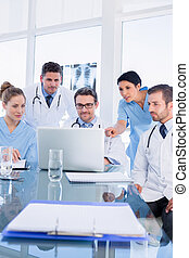 Concentrated medical team using laptop together
