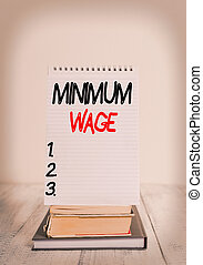 Conceptual hand writing showing Minimum Wage. Business photo text the lowest wage permitted by law or by a special agreement Front view stacked books spiral note book on vintage wooden table.