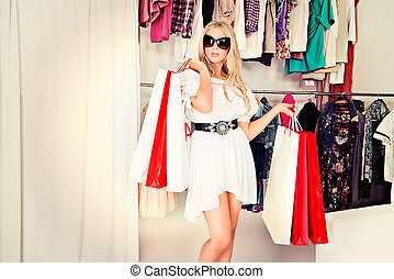 Fashionable lady standing with a lot of shopping bags in a store.