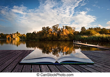 Creative concept image of sunset sky reflected in Autumn Fall lake in pages of book