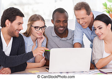 Creative team working on project. Group of business people in casual wear sitting together at the table and looking at the laptop
