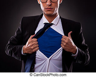 Cropped view of young business man tearing off his shirt on black background