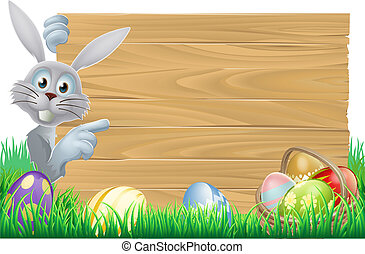 White Easter rabbit bunny pointing at a sign, with chocolate Easter eggs and basket
