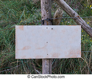 empty blank signboard plate on a pole to put whatever you want in a nature landscape with grass