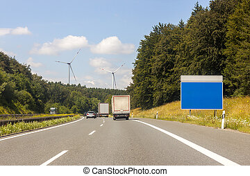 Empty blue sign board at the roadside on freeway in summer landscape. Add your own text. Strategy blank sign on a highway as a clear plan and solutions for business leadership with copy space. Cars, trucks and lorries on the road.