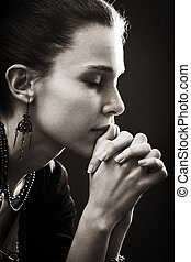 Faith and religion - spiritual woman praying in darkness
