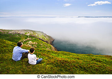 Father and son looking at foggy ocean view in Newfoundland