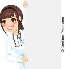 Beautiful happy professional female doctor peeking out of a blank billboard