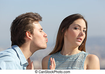 Friend zone concept with a man trying to kiss a woman and she rejecting him