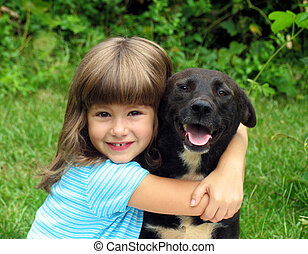 Little girl, smiling, with black dog in an outdoor setting