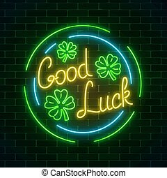 Glowing neon sign with geed luck wish and four-leaf clovers in circle frames on dark brick wall background.