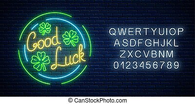 Glowing neon sign with geed luck wish and four-leaf clovers in circle frames with alphabet. Three leaves of shamrock.
